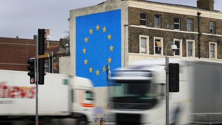 Lorries pass the Brexit-inspired mural by artist Banksy in Dover