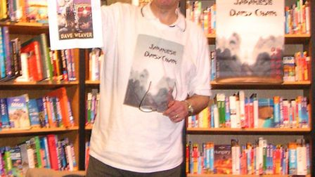 Dave Weaver displaying the artwork for his third novel