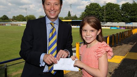 St Albans City FC owner Lawrence Levy receives some money from Isobel Burwood, 7 who sold some of he