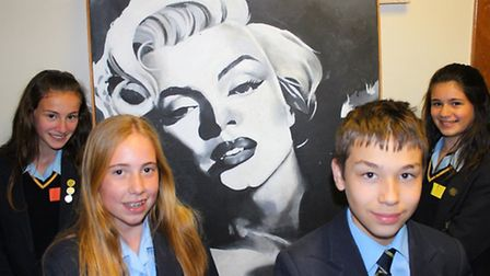 Students with raffle prize, a painting of Marilyn Monroe