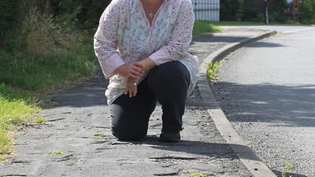 Lucy Stevenson on a pavement in Guilden Morden which is in a bad state