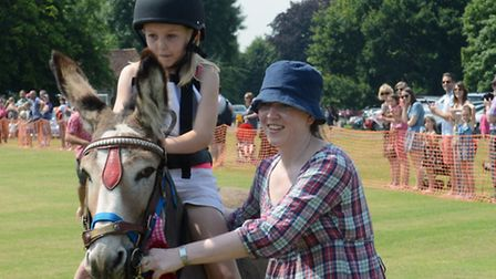 Donkeys and riders are led to the finish line at the Eltisley derby.