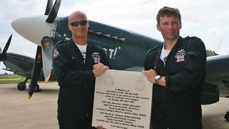 RAF pilots holding a plaque in memory of Harold Williams and John Brewster