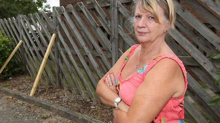 Valerie Hargrave with a fence which has been propped back up again by the council after falling