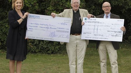 Canon Shamus Williams receives cheques from (left) Jane Allton of St Mary's Church Restoration Commi