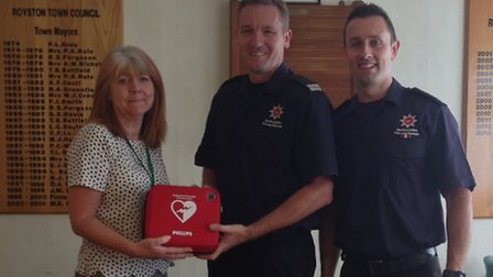 Town clerk Susan Thornton-Bjork receiving the kit from Ray Constant and fire fighter Keith Brown