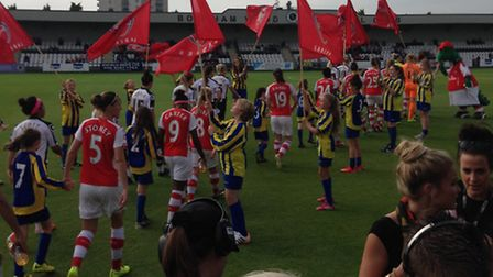 Harvesters girls form a guard of honour for Arsenal ladies.