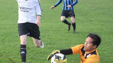 NBOB 90 keeper saves as Bradmore Rovers' Anthony Ansell moves in.