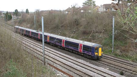 A train goes past houses in Harpenden