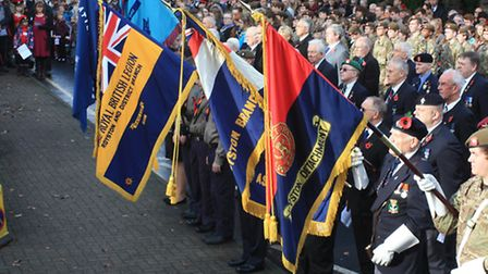 Servicemen and women hold flags in remembrance. Credit: Clive Porter.