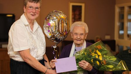 Barbara Charter, chair person of Forget-me-Not presents flowers to Babs Self, for her 100th Birthday