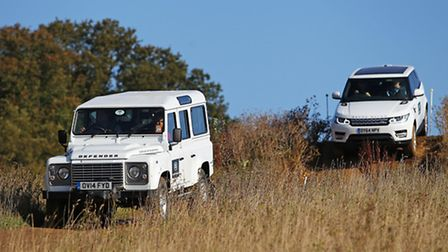 A Land Rover Defender and a Range Rover Evoque on the course