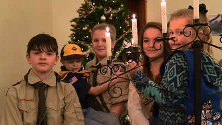 Lights from the Bethlehem peace candle with (from left) Hyden, Max, Cameron, Kaitlin and Pearl.