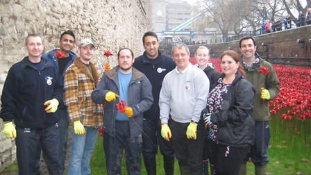 Simon Barons, left, removing the poppies at the Tower of London