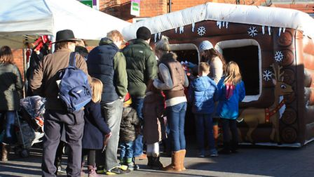 Crowds queue to meet Santa in his grotto by Clive Porter
