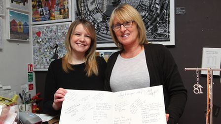 Huttons assistant manager Tania Lane and manager Landy Kelly with a book of messages from customers,