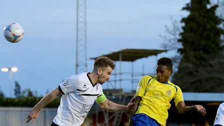 Omar Beckles directs his header towards goal under pressure from Ben Martin. Picture: Leigh Page