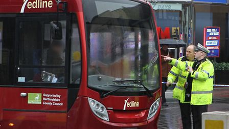 Police inspect the damage to the windscreen on the front of the bus