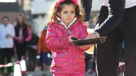 A young girl flips her pancake with a little bit of help in the pancake race