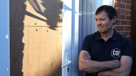 Terry Oram stands next to the door of his house which was broken in