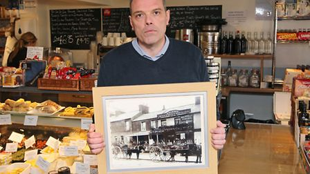 Buongiorno Italia owner Tony Picciuto holds a photo showing his shop in the 1800's but now his landl