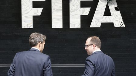 Two men talk to each other in front of the FIFA logo at the FIFA headquarters in Zurich, Switzerland