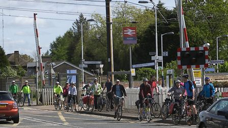 Cyclists crossing next to traffic due to broken pedestrian gate.
