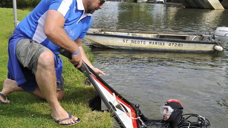 Diving instructor Danny Hyett takes a road sign from diver James Faye.
