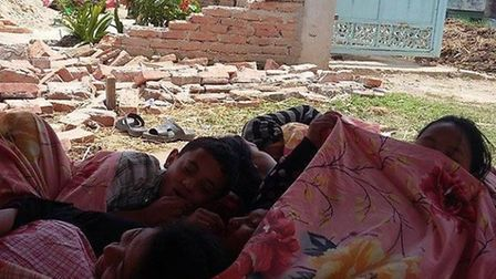 Children sleeping next to the rubble.
