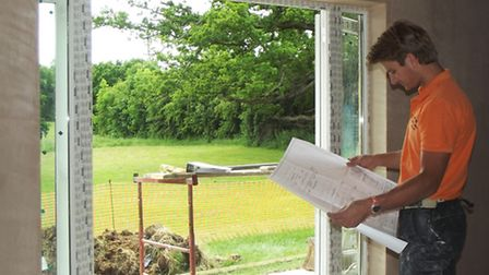 Harry Hunt checking plans for Harpenden Town's club house with the new south facing entrance overloo