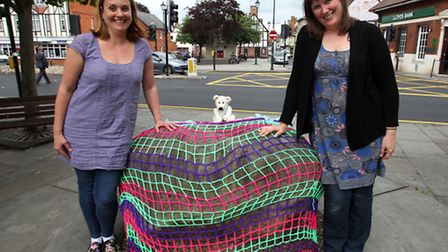 Anne Walls and Laura Whitford, with their giant tea cosy on the Roy Stone in Royston