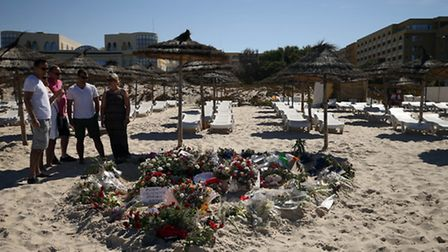 People pay their respects on the beach near the RIU Imperial Marhaba hotel in Sousse, Tunisia, as Br