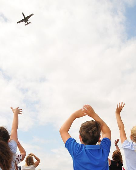 Steeple Morden church of England year 4 class wave as two A-10C Thunderbolt II fly past the memorial