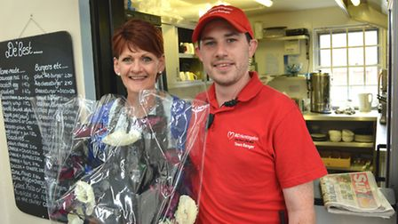 Cafe owner Debbie Ross-Harwood, recieves flowers from Town Ranger Nathan Boreland, after saving a ma