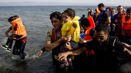 Syrian migrants arrive at the coast on a dinghy after crossing from Turkey, at the island of Lesbos,