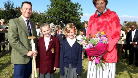 Ian Pigott, founder of Farmschool, Gracie Pigott and Lucy Bates hand flowers to Lord-Lieutenant of H