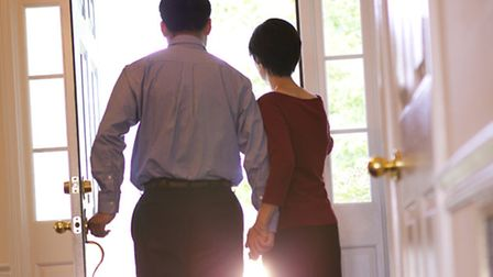 Rear view of a couple welcoming someone at the front door of their home