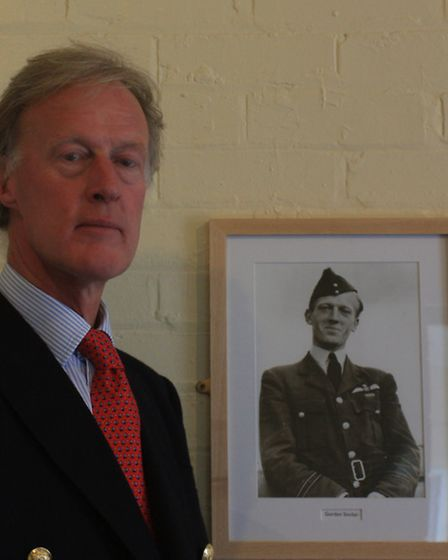 Alan Sinclair alongside the photgraph of his father, Gordon. PICTURE: Clive Porter.