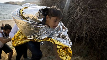 A young Syrian boy, wrapped with a thermal blanket, arrives with others after crossing aboard a ding