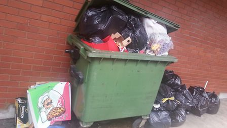 Rubbish is being fly-tipped around the residents' sole bin, behind flats at French Row