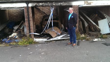 Cllr Tom Clegg at the scene of the burned out garages in St Albans