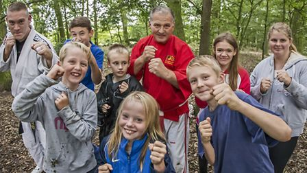 Ian Williams painting supervisor Cliff Witcher, fourth from right, with youngsters from Loves Farm y