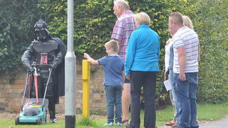 Visitors to the Foxton Scarecrow Festival watch a lawn mowing Darth Vader in action.