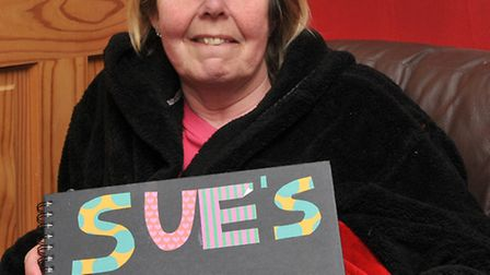 Susan Webster with a memory book made by staff at Addenbrookes hospital has returned home after suff