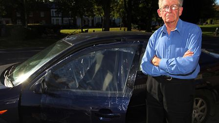 Clive Porter stands next to the damaged car window where his camera was stolen from