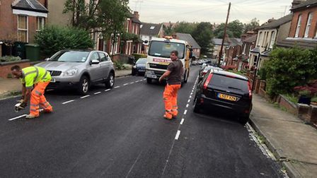 Colas workers painting white and yellow lines while cars remain parked.