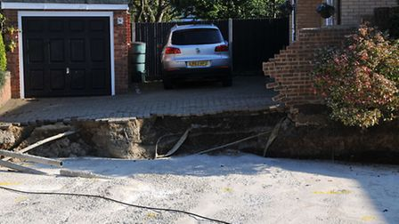 A car is trapped on its driveway by the sinkhole