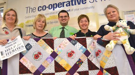 St Ives Co-Op, staff member (l-r) Alison Bailey, fundraising for the poppy appeal, with the quilt s