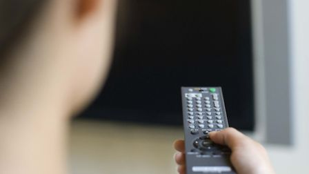 Woman using television remote control.