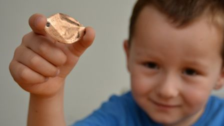 Metal detector enthusiast Ryan Lynam, from St Ives, finds gold pendant, son Tommy shows it off,